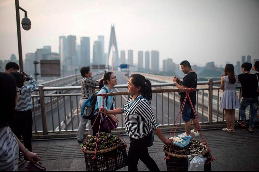 A woman carries food to sell as tourists enjoy the view of the Yangtze river in Chongqing on May 31, 2017.