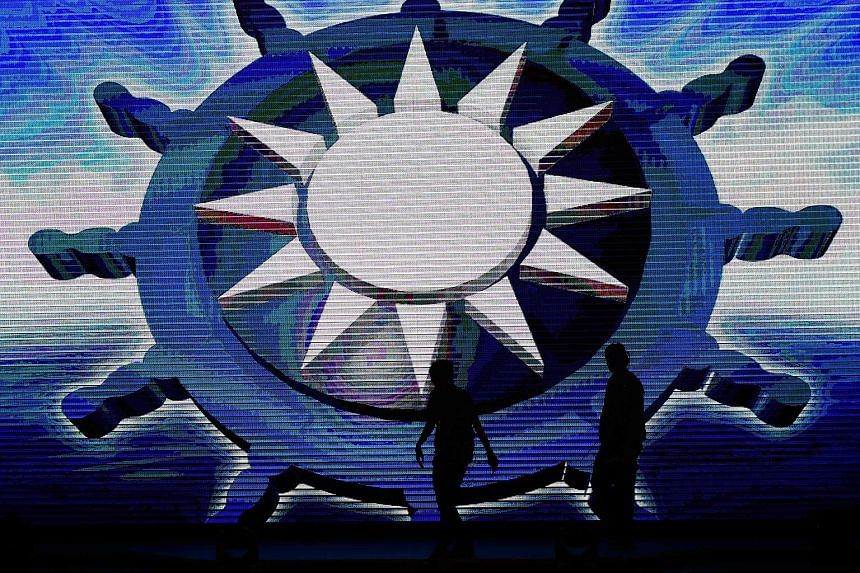 Two ruling Kuomintang (KMT) members walk past a giant KMT logo.