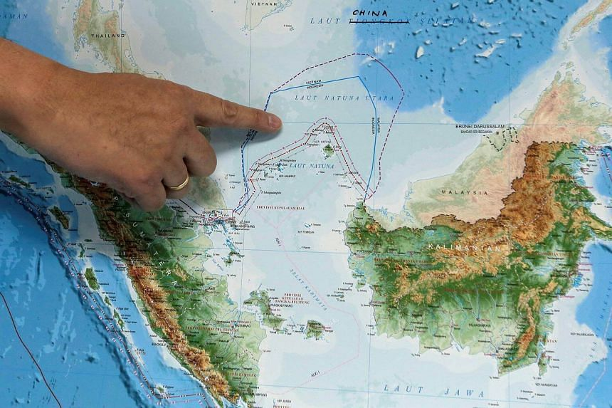 Indonesia's Deputy Minister for Maritime Affairs Arif Havas Oegroseno points at the location of North Natuna Sea on a new map of Indonesia on July 14, 2017.