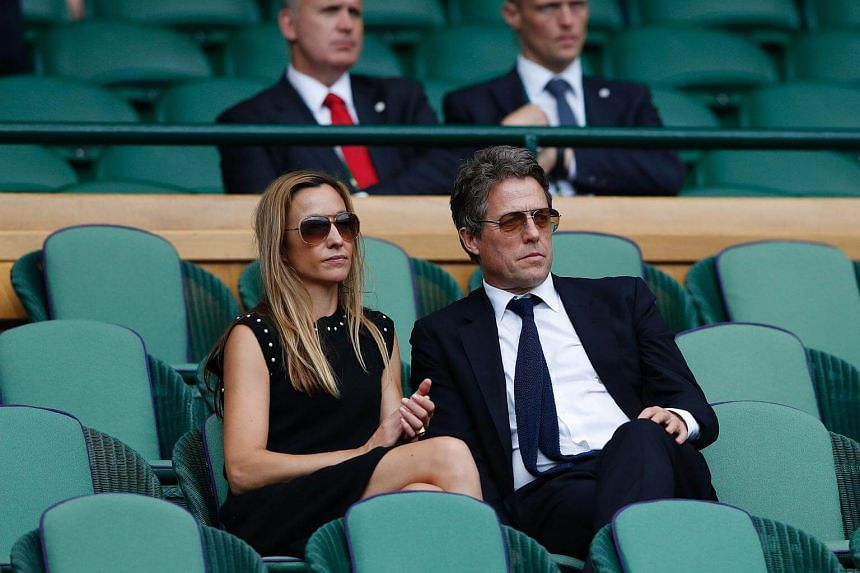 Actor Hugh Grant and Anna Eberstein sit in the Royal box on Centre Court in Wimbledon on July 16, 2017.