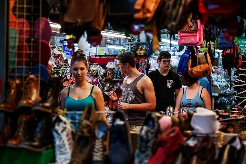 Tourists browse market stalls in Chiang Mai, Thailand, on June 16, 2017.
