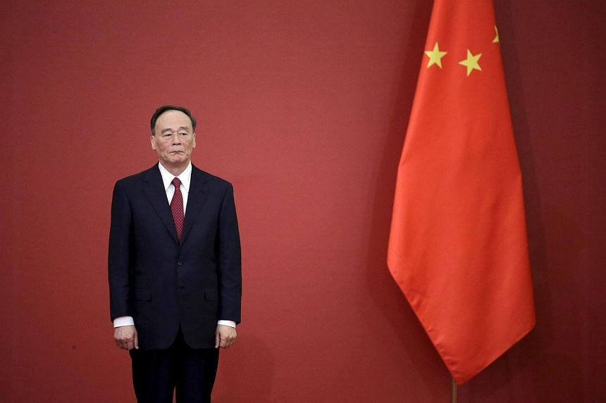 China's Politburo Standing Committee member Wang Qishan, stands next to a Chinese flag during a medal ceremony at the Great Hall of the People in Beijing, on Sept 2, 2015.