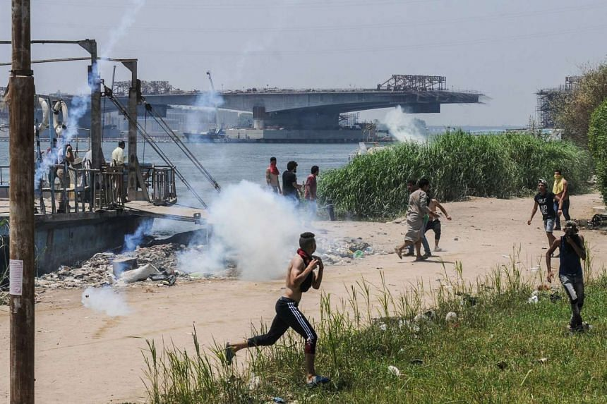 Egyptians run for cover from tear gas during clashes with security forces in the Nile island of Warraq in Giza province, north of the capital Cairo, on July 16, 2017.