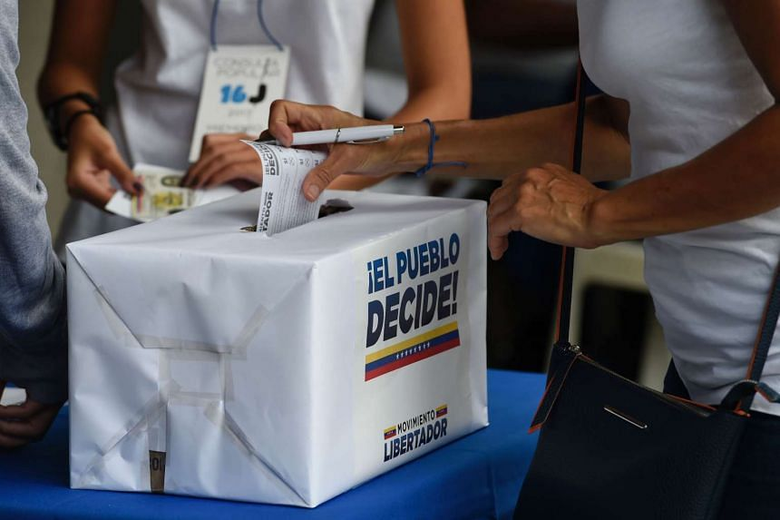 A woman casts her ballot on July 16, 2017 in Caracas, in an opposition-organised vote to measure public support for President Nicolas Maduro's plan to rewrite the constitution, against a backdrop of worsening political violence.