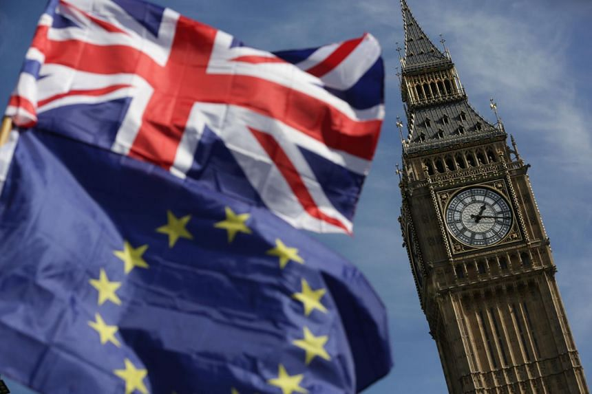 An EU flag and a Union flag held by a demonstrator is seen with Elizabeth Tower (Big Ben).