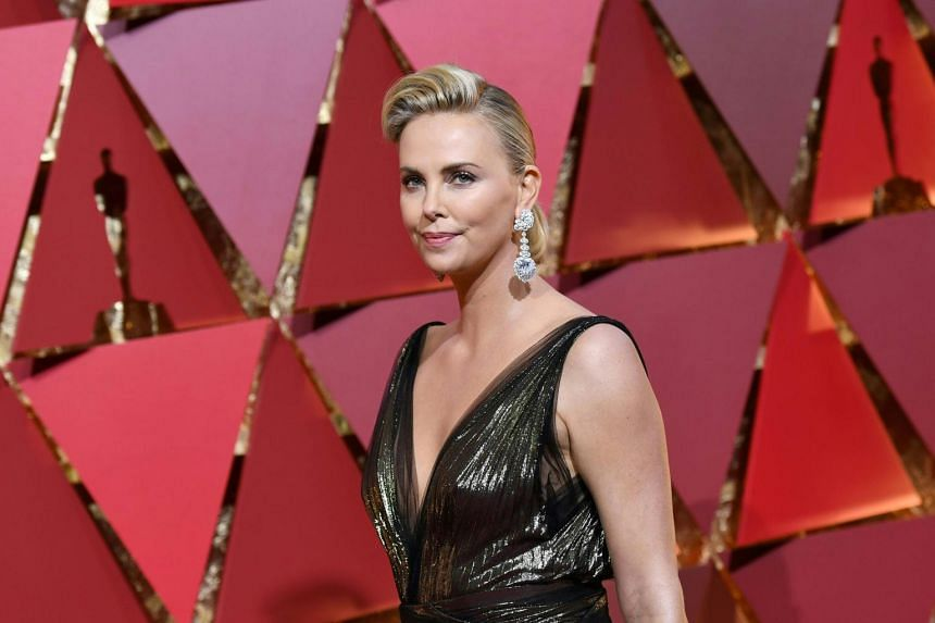 US actress Charlize Theron posing as she arrives on the red carpet for the 89th Oscars, on Feb 26, 2017.