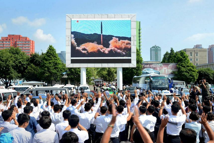 People watch a huge screen showing the test launch of intercontinental ballistic missile Hwasong-14 in this undated photo released by North Korea's Korean Central News Agency (KCNA).