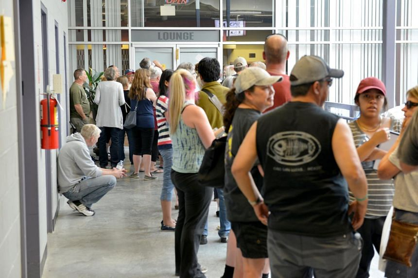 Residents of the nearby towns of Cache Creek and Ashcroft who have fled wild fires waiting to be registered at an evacuation center in Kamloops, BC, Canada, on July 8, 2017.