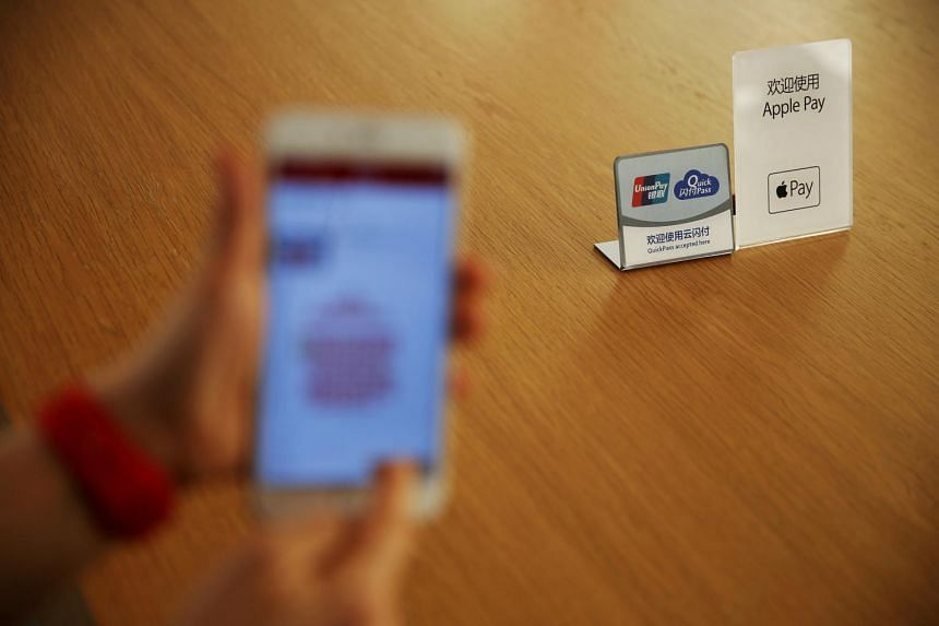 An employee uses the Apple iPhone to demonstrate to reporters how to pay using the Apple Pay service at an Apple store in Beijing.