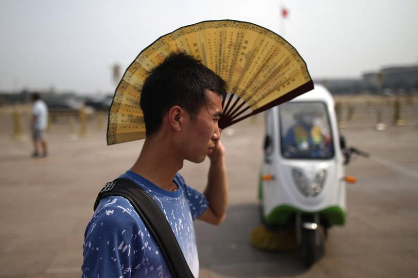 A Chinese man uses a fan to provide shade in front of the Tiananmen Gate on a hot day in Beijing.