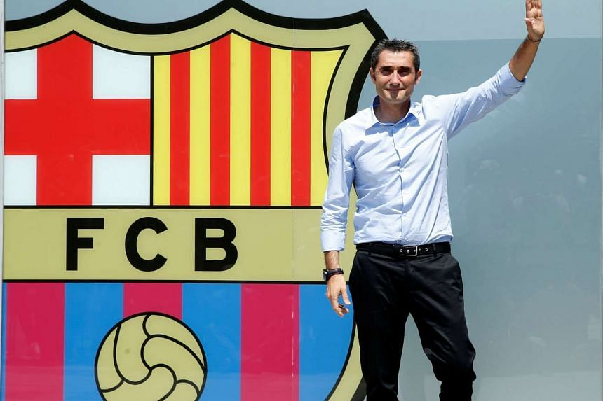 Coach Ernesto Valverde poses in front of FC Barcelona's giant logo at their offices at Camp Nou Stadium in Barcelona, Spain on May 31, 2017.