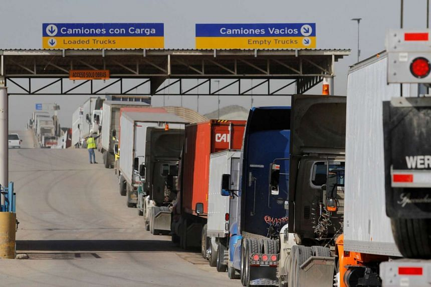 Trucks wait in a long queue for border customs control to cross into the US at the Otay border crossing in Tijuana, Mexico.