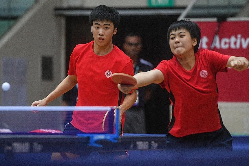 Goi Rui Xuan hits a return during the Asean Schools Games mixed doubles final as her partner Gerald Yu looks on.