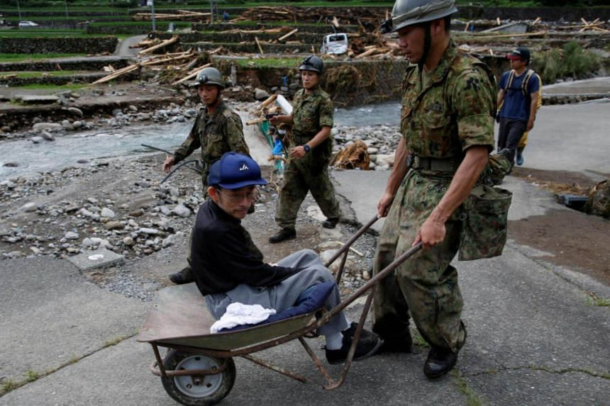 A local resident is aided by Japanese Self-Defense Force soldiers during the evacuation from an isolated area hit by heavy rain in Toho village, Fukuoka Prefecture, Japan on July 8, 2017.