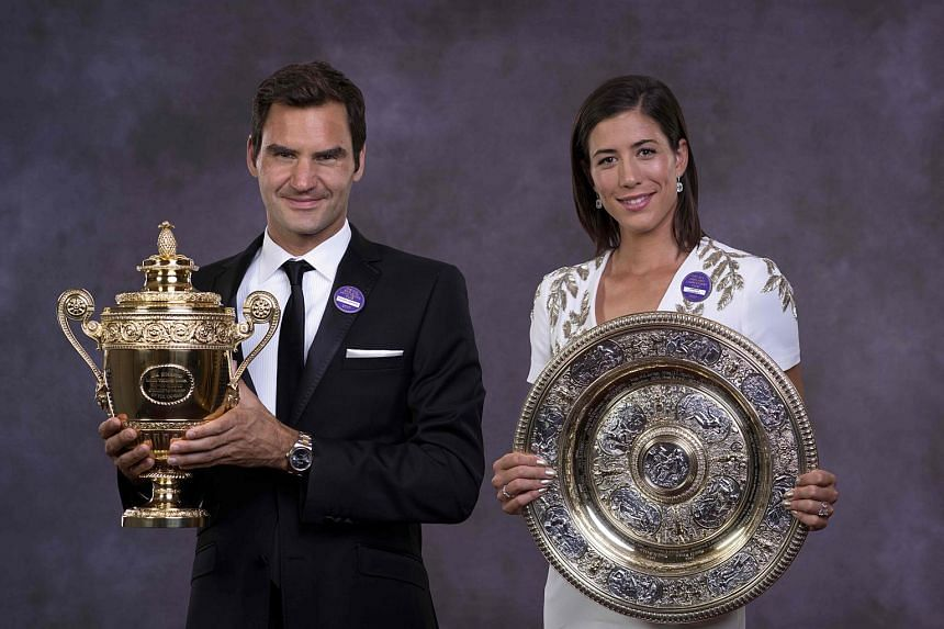 A handout composite picture taken on July 16, 2017 shows 2017 Wimbledon Men's and Women's singles champions, Switzerland's Roger Federer and Spain's Garbine Muguruza posing with their trophies at the Champions Dinner in central London.