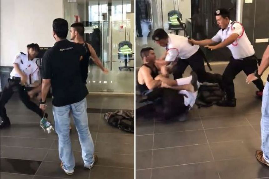 The man aims a kick at the security guard (left) before two other guards intervene to subdue him.