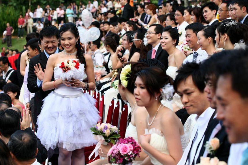 Couples attending a mass wedding event at the Singapore Botanic Gardens.
