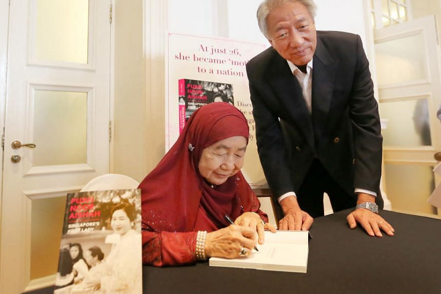 Puan Noor Aishah autographs a copy of the book for Deputy Prime Minister Teo Chee Hean.