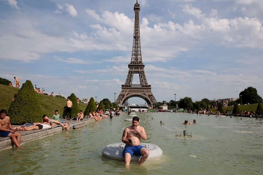 A man speaks on the phone as he sits in Fountain of Warsaw at the Gardens of the Trocadero with the Eiffel Tower on the back ground during warm temperatures in Paris on May 27, 2017.