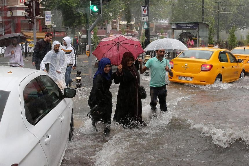 Pedestrians struggle to cross a flooded street after torrential rain in Istanbul, on July 18, 2017.