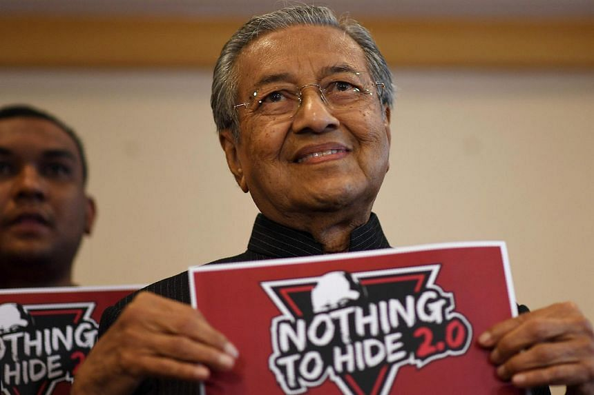 "Malaysia's former prime minister Mahathir Mohamad holds a placard for the second ""Nothing To Hide"" public debate following a press conference in Putrajaya on July 18, 2017."