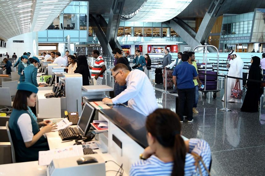 Passengers check-in at the Hamad International Airport in Doha on June 7, 2017.