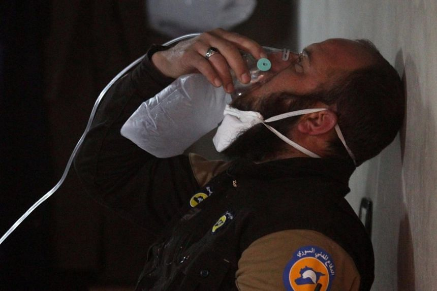 A civil defence member breathes through an oxygen mask, after what rescue workers described as a suspected gas attack in the town of Khan Sheikhoun in rebel-held Idlib, Syria on April 4, 2017.