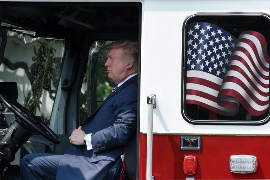 """President Donald Trump examines a fire truck from Wisconsin-based manufacturer Pierce during a """"Made in America"""" product showcase event on the South Lawn at the White House."""