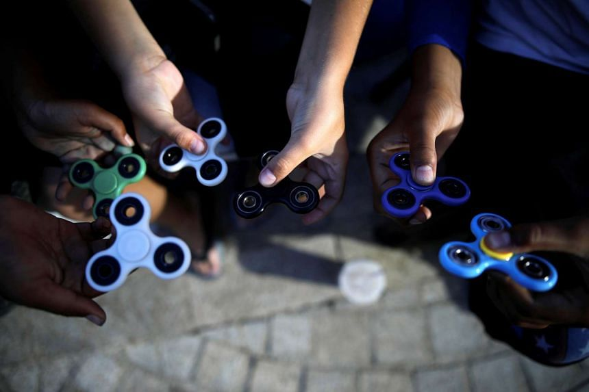 Children perform tricks using fidget spinners during a contest held in Ashdod.
