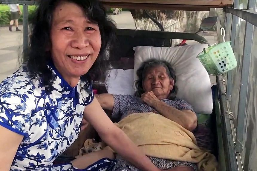 """In a video clip that has gone viral in China, the man is shown in a cheongsam with wavy, shoulder-length hair tending to his elderly mother. Those who viewed the clip were moved by his actions, hailing him as a """"filial son""""."""