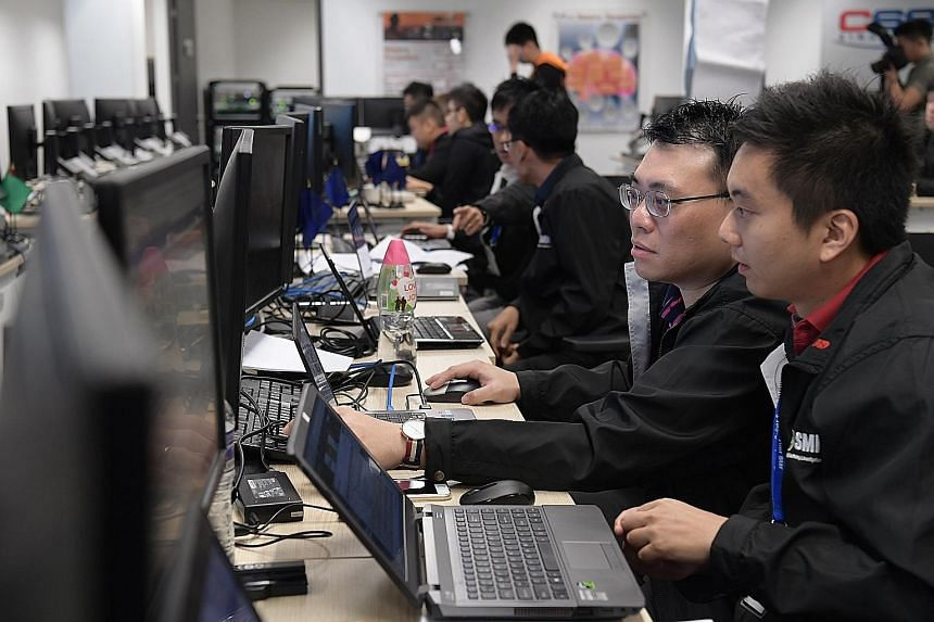 Public agencies' National Cyber Incident Response Teams taking part in a cyber-attack simulation during Exercise Cyber Star at the Cyber Security Agency of Singapore's headquarters yesterday.