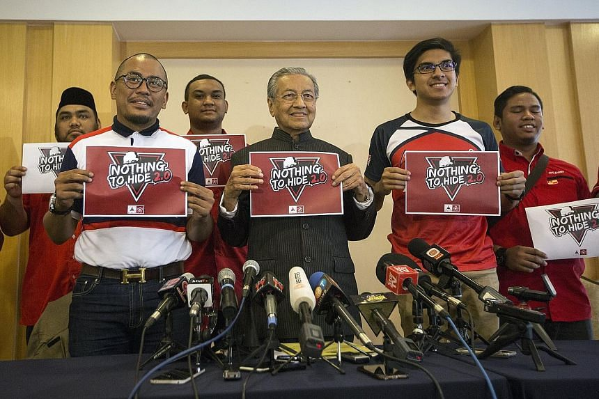 Dr Mahathir Mohamad (centre) holding up a poster for a debate he wants to hold with Prime Minister Najib Razak on alleged financial scandals under their respective premierships at a press conference yesterday.