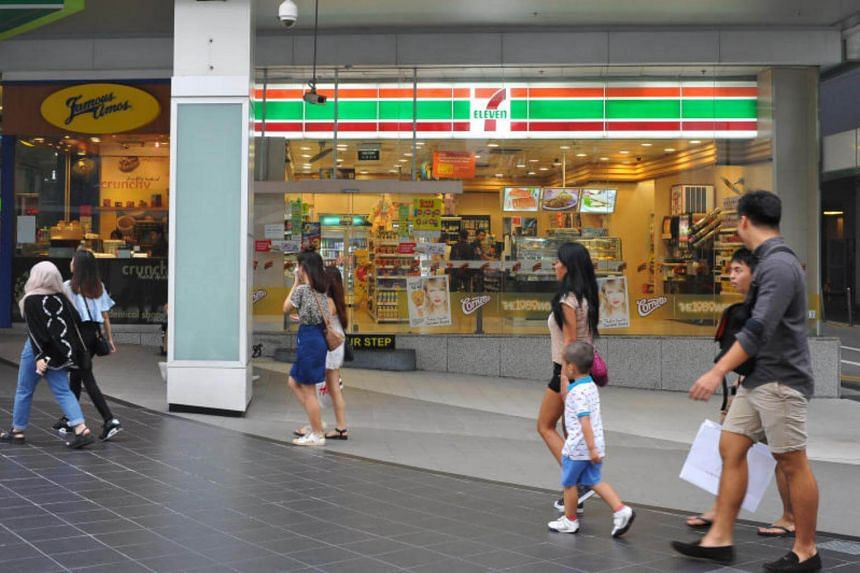 People walk past a 7-Eleven store at Cathay Cineleisure Orchard.