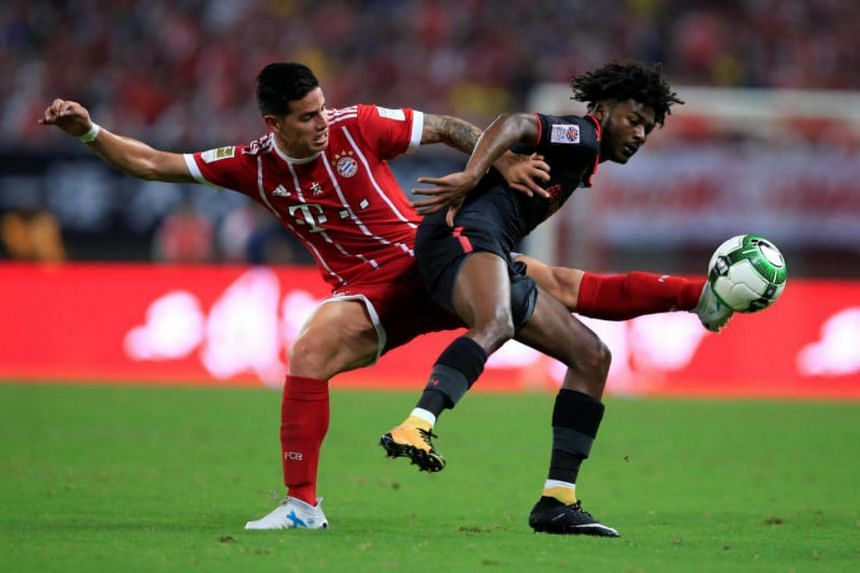 Bayern Munich's James Rodriguez (in red) in action with Arsenal's Ainsley Maitland-Niles .