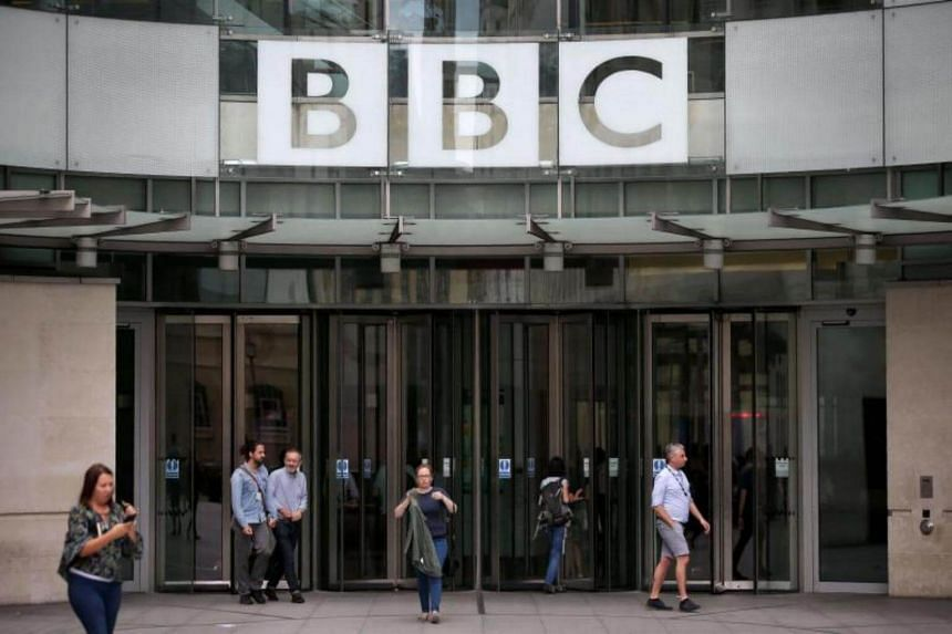 Staff and visitors walk outside the headquarters of the British Broadcasting Corporation (BBC) in central London on July 19, 2017.