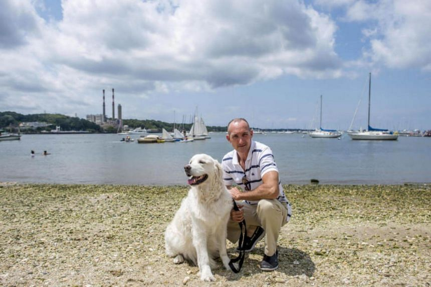 Mark Freeley with Storm, his six-year-old English Labrador retriever, who pulled a fawn from Port Jefferson Harbor several days ago, in Port Jefferson, NY on July 18, 2017.