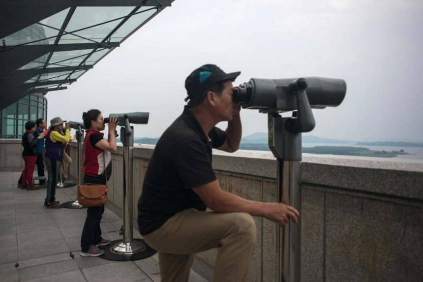 Visitors look through binoculars towards North Korea at the Odusan observatory, near the Demilitarized Zone (DMZ) separating North and South Korea, in Paju on June 20, 2017.