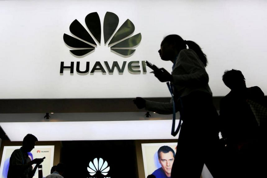 People walk past a sign board of Huawei at the Consumer Electronics Show Asia 2016 in Shanghai, China May 12, 2016.