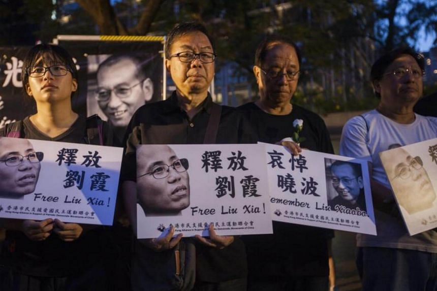 Members of the Hong Kong Alliance in Support of Patriotic Democratic Movements of China hold a minute silence in Chater Garden on July 15, 2017.