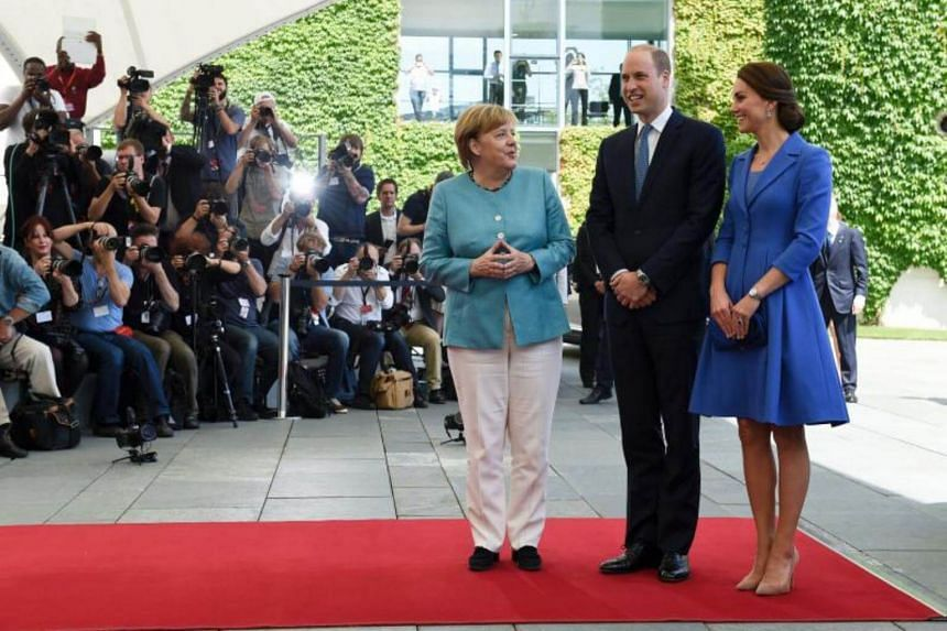 Britain's Prince William (centre), Duke of Cambridge, and his wife Kate, the Duchess of Cambridge are greeted by German Chancellor Angela Merkel (right) upon their arrival at the Chancellery in Berlin on July 19, 2017.