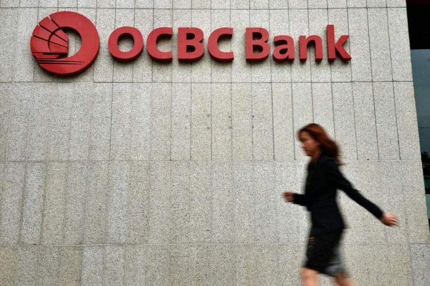 A lady walking past the OCBC Bank logo on the bank's building at Chulia Street.