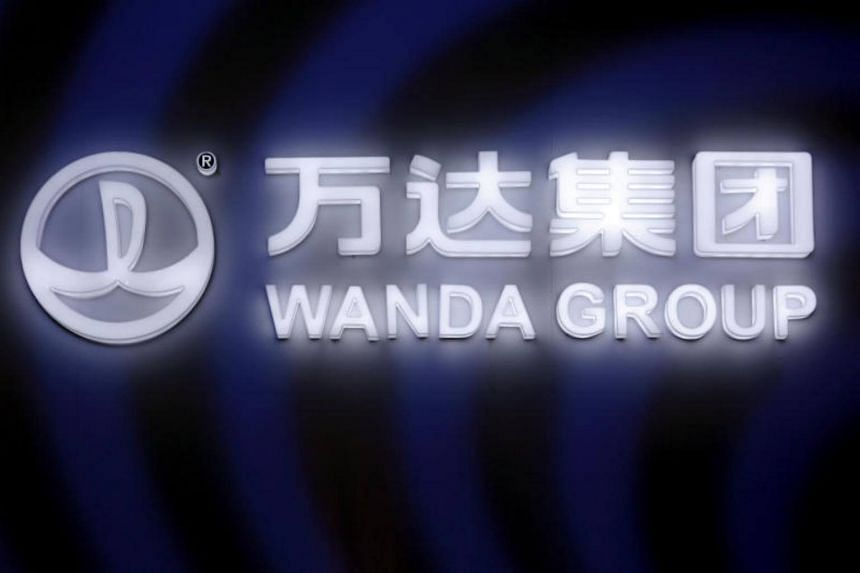 A sign of Dalian Wanda Group in China glows during an event in Beijing, China.