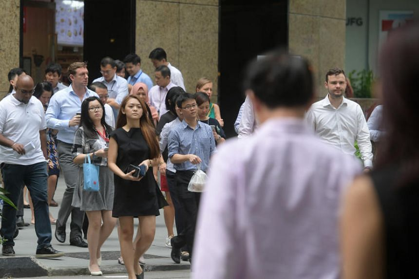 Office workers walk across the street at the Central Business District in Singapore.