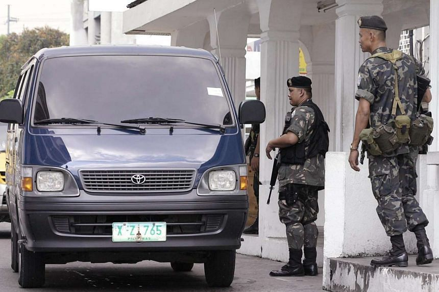 Members of the elite Presidential Security Group in full combat gear inspect a vehicle passing through a gate of the Malacanang palace in Manila,  on July 8, 2015.