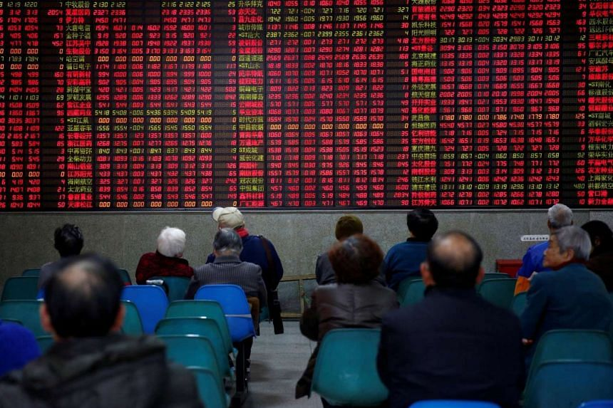 Investors look at an electronic board showing stock information on the first trading day after the New Year holiday at a brokerage house in Shanghai.