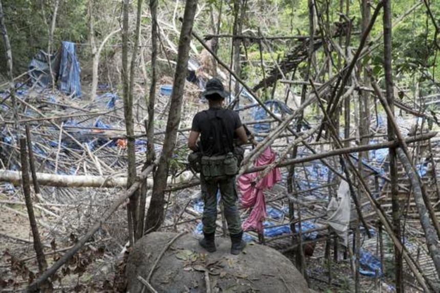 A policeman watching over an abandoned human-trafficking camp in the jungle close to the Thailand border at Bukit Wang Burma in northern Malaysia on May 26, 2015.