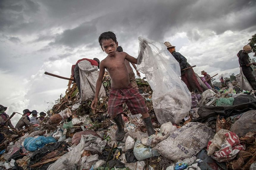 A young scavenger boy grabs plastic between tons of trash in the Anlong Pi on June 11, 2014 in Siem Reap, Cambodia.