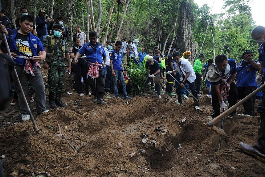 Rescue workers and forensic officials uncovering skeletons from mass graves of human trafficking victims at an abandoned jungle camp located by the Thai-Malaysian border in May 2015.