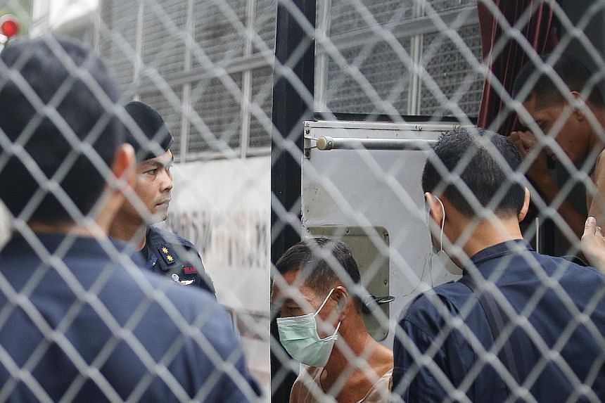 Senior military officer Manas Kongpan was declared guilty of transnational organised crime by the court. Thai police officers standing guard as suspects in a human trafficking case arrive at the criminal court in Bangkok yesterday. A landmark trial i