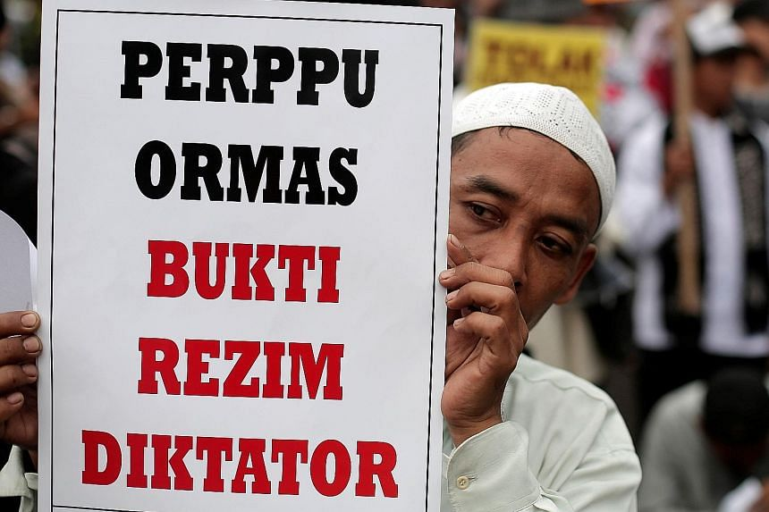 """A protester holding up a placard which reads """"Regulation for mass organisations is evidence of a dictatorial regime"""" during a demonstration in Jakarta on Tuesday."""